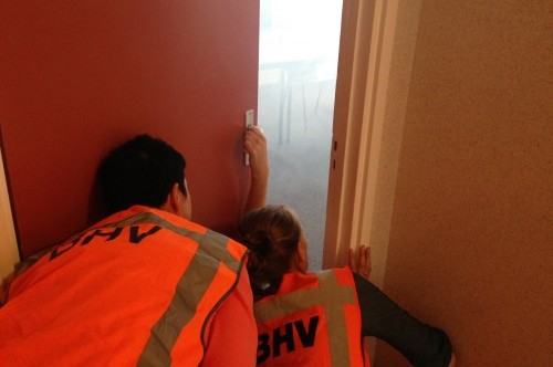cursisten tijdens de bhv cursus onderzoeken een brandalarm